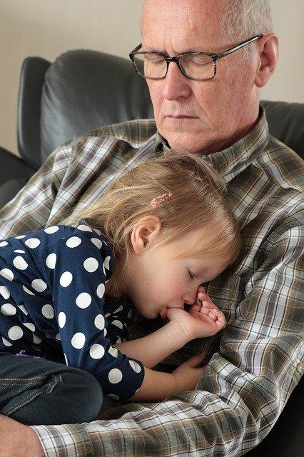 A young girl has fallen asleep on her grandfather's lap while sucking her thumb. Grandpa is also taking a nap as he holds his granddaughter.