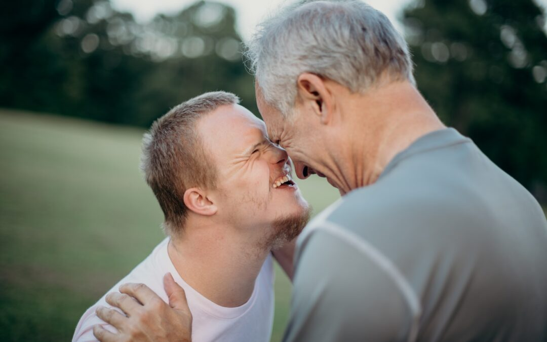 A father embraces and touches his nose to the face of his adult son who has downs syndrome.